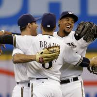 Photo - Milwaukee Brewers' Logan Schaffer, left, Ryan Braun and Carlos Gomez react after beating the Atlanta Braves in the Opening day baseball game Monday, March 31, 2014, in Milwaukee. The Brewers won 2-0.  (AP Photo/Jeffrey Phelps)