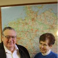 Photo - Claus and Helga Greiner in front of a map of Germany in the German American Society of Tulsa Center.  STAFF PHOTO BY DAVID CHRISTOPHER
