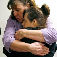 Photo - Debbie Scott, an employee at Daily Living Centers, gets a hug from Dana Harris, a client, as Scott greets her at the door in the morning at Daily Living Centers' north Rockwell location in Bethany on Tuesday, Nov. 24, 2009. By John Clanton, The Oklahoman