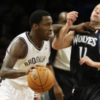 Photo -   Brooklyn Nets' Tyshawn Taylor, left, drives past Minnesota Timberwolves' Jose Juan Barea during the first half of an NBA basketball game, Monday, Nov. 5, 2012, in New York. (AP Photo/Frank Franklin II)
