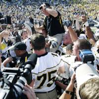 Photo - FILE - In this Sept. 1, 2007, file photo, Appalachian State coach Jerry Moore is carried off the field at Michigan Stadium by his players after they upset No. 5 Michigan 34-32 in an NCAA college football game in Ann Arbor, Mich. Michigan is opening its 2014 season with Appalachian State this week, rekindling flashbacks to the day the Wolverines were on the wrong end of one of the biggest upsets in college football history.  (AP Photo/Duane Burleson, File)