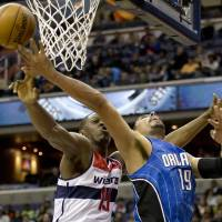 Photo - Washington Wizards Kevin Seraphin (13) blocks Orlando Magic power forward Gustavo Ayon (19) from scoring during the second quarter of an NBA basketball game at the Verizon Center in Washington, Friday, Dec. 28, 2012. (AP Photo/Jacquelyn Martin)