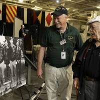 Photo -   Lt. Col. Edward Saylor, right, talks with USS Hornet volunteer Roger Felton as they look at an old photograph before a news conference to commemorate the 70th Anniversary of the Tokyo attack by the Doolittle Raiders on the USS Hornet in Alameda, Calif., Saturday, May 5, 2012. Survivors of a daring World War II aerial bombing of Japan are gathering in Alameda on the 70th anniversary of the attack. The