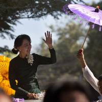 Photo - Opposition leader Aung San Suu Kyi waves to her supporters as she arrives in Monywa town, northwestern Myanmar, Thursday, Nov. 29, 2012. Security forces used water cannons, tear gas and smoke bombs Thursday to clear protesters from a copper mine in northwestern Myanmar, wounding villagers and Buddhist monks just hours before Suu Kyi arrived in the area to hear their grievances. (AP Photo/Gemunu Amarasinghe)