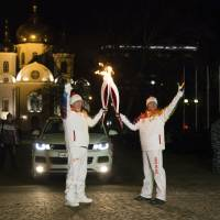 Photo - In this Feb. 4, 2014 photo provided by Olympictorch2014.com, Olympic torch bearers Eldar Khalilov and Gilley Geremi, left, hold Olympic torches during the torch relay in Krasnodar, the capital city of the Krasnodar region, Russia.  The relay for the Sochi Winter Games, which began on Oct. 7 2013 in Moscow, will pass through many cities that showcase the historical, cultural and ethnic richness of Russia. (AP Photo/Olympictorch2014.com) EDITORIAL USE ONLY