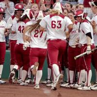 Photo - Sooner Erica Sampson (63) and the two runners she drove in are greeted at home plate after a home run with two base runners on as the University of Oklahoma (OU) Sooners play the Oklahoma State University Cowgirls in NCAA college softball at Marita Hines Field on Wednesday, April 25, 2012, in Norman, Okla. Photo by Steve Sisney, The Oklahoman