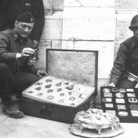 """Photo - This photo provided by The Monuments Men Foundation for the Preservation of Art of Dallas, shows Monuments Man James Rorimer, left, and Sgt. Antonio Valim examining valuable art objects at Neuschwanstein Castle in Germany which were stolen from the Rothschild collection in France by the ERR and found in the castle in May of 1945. Rorimer, a curator at the Metropolitan Museum of Art before the war who eventually became its director after returning, went on to achieve great success, helping to discover where works of art looted by the Nazis were tucked away across Europe. In the upcoming movie """"The Monuments Men,"""" Matt Damon portrays a character inspired by the real-life Rorimer, who died in 1966 at the age of 60.  (AP Photo/National Archives and Records Administration)"""