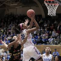 Photo - Duke's Oderah Chidom (22) drives to the basket ahead of Maryland's Shatori Walker-Kimbrough (32) during the first half of an NCAA college basketball game in Durham, N.C., Monday, Feb. 17, 2014. (AP Photo/Ted Richardson)