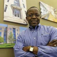 Photo - Mel Gravely, president of TriVersity Construction, poses in his office in front of some paintings of work his company has done, Wednesday, April 16, 2014, in Cincinnati. Gravely's company joined a program called a minority business accelerator even before he bought a controlling interest in the Cincinnati-based company in 2006. It helped the company get started and win contracts that have helped Triversity's revenue double. (AP Photo/Al Behrman)