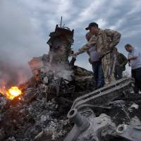 Photo - FILE - In this Thursday, July 17, 2014 file photo, people inspect the crash site of a passenger plane near the village of Grabovo, Ukraine. All 298 people aboard the Malaysia Airlines Flight 17 traveling from Amsterdam to Kuala Lumpur were killed. (AP Photo/Dmitry Lovetsky)