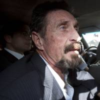 Photo - Software company founder John McAfee leaves an immigration detention center for the La Aurora international airport in Guatemala City, Wednesday Dec. 12, 2012. McAfee, who is being deported to the U.S., was detained last week for immigration violations after he sneaked into Guatemala from neighboring Belize, where authorities sought to question him about the murder of his neighbor. (AP Photo/Moises Castillo)