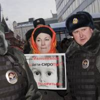 Photo - Police officers detain a protester near the State Duma, in Moscow, Russia, Wednesday, Dec. 19, 2012. People picket parliament's lower chamber, to protest against planned debate of an amendment that would ban Americans from adopting Russian children. The poster reads: Are orphans guilty of Magnitsky's death ? Stop putting shame on yourselves! Sergei Magnitsky, a Russian lawyer who was arrested by the officials he accused of a $230 million tax fraud. He was repeatedly denied medical treatment and in 2009 died in jail. (AP Photo/Novaya Gazeta, Yevgeny Feldman)