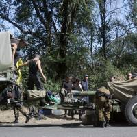 Photo - Ukrainian soldiers park their hardware on roadside as they are waiting for the start of the march into the town of Mariupol, eastern Ukraine, Wednesday, Aug. 27, 2014. Heavy shelling hit a town of Novoazovsk in southeastern Ukraine on Wednesday, the third day of an assault that has forced government troops to spread their ranks thinner along the Russian border. Ukraine claimed the shelling was coming both from pro-Russian separatists and from Russia itself. (AP Photo/Sergei Grits)