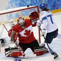 Photo - Goalkeeper Shannon Szabados of Canada blocks a shot at the goal under pressure from Susanna Tapani of Finland during the third period of the 2014 Winter Olympics women's ice hockey game at Shayba Arena, Monday, Feb. 10, 2014, in Sochi, Russia. Canada defeated Finland 3-0. (AP Photo/Petr David Josek)