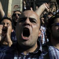 Photo -   Egyptian protesters chant anti-ruling military council slogans during a rally demanding the release of fellow activists, detained during the army operation that dispersed a protest in front of the Ministry of Defense, in Cairo, Egypt Sunday, May 6, 2012. (AP Photo/Nasser Nasser)