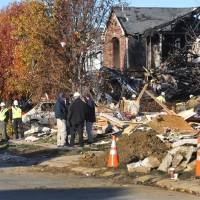 Photo -   Utility workers, and investigators stand outside destroyed homes on Fieldfare Way in the Richmond Hills subdivision Monday, Nov. 12, 2012. An explosion, originating on Fieldfare Way, destroyed or damaged as many as 80 structures in the subdivision late Saturday night November 10, 2012. (AP Photo/The Indianapolis Star, Joe Vitti)