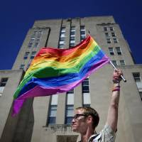 Photo - Gary Jones, 37, Racine, holds aloft the rainbow striped gay and lesbian pride flag in front of the Racine County Courthouse on Friday, June 13, 2014, in Racine, Wis., during a rally in support of gay marriage after the county has still refused to grant marriage licenses to same-sex couples despite a judge's ruling that the state ban on gay marriage is unconstitutional. Racine County is one of a minority of counties in Wisconsin currently continuing to refuse to issue marriage licenses to same-sex couples. (AP Photo by Scott Anderson, Journal Times)