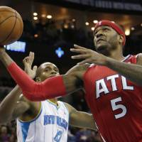 Photo - Atlanta Hawks small forward Josh Smith (5) shoots past the defense of New Orleans Hornets small forward Lance Thomas (42)during the second quarter of an NBA basketball game at the New Orleans Arena in New Orleans Tuesday, Jan. 1, 2013. (AP Photo/Dave Martin)