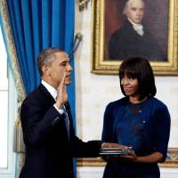 Photo - President Barack Obama is officially sworn-in by Chief Justice John Roberts, not pictured, in the Blue Room of the White House Sunday, Jan. 20, 2013, in Washington, as first lady Michelle Obama holds the Robinson Family Bible. (AP Photo/Doug Mills, The New York Times, Pool)