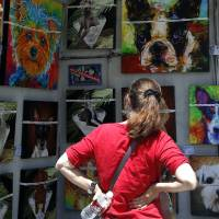 Photo -  Kimberly Weiss checks out Gregg Billman's artwork Sunday at the Festival of the Arts. Photo by Sarah Phipps, The Oklahoman   SARAH PHIPPS -