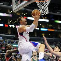 Photo - Los Angeles Clippers forward Blake Griffin, center, battles by Milwaukee Bucks forward Ekpe Udoh, left, guard J.J. Redick (5) and forward Ersan Ilyasova (7), of Turkey, for a reverse dunk in the first half of an NBA basketball game, Wednesday, March 6, 2013, in Los Angeles.(AP Photo/Gus Ruelas)