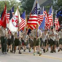 Photo - Boy Scouts march with flags during the annual LibertyFest Fourth of July Parade in downtown Edmond, OK, Thursday, July 4, 2013, Photo by Paul Hellstern, The Oklahoman