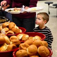 Photo - Owen Atteberry, 3, watches his mom, Kristin, put food on his plate as they go through the serving line at Putnam City West High School on Saturday. PHOTO BY JIM BECKEL, THE OKLAHOMAN  JIM BECKEL - THE OKLAHOMAN