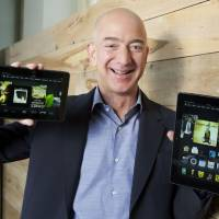 Photo - In this image by Amazon, Amazon.com Founder and CEO Jeff Bezos holds the Kindle Fire HDX 8.9'', right, and Kindle Fire HDX 7'' tablet.  Stephen Brashear