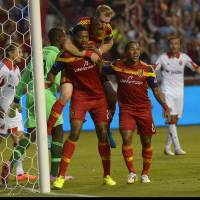 Photo - Real Salt Lake defender Chris Schuler (28) reacts to his second goal with defender Nat Borchers (6) and forward Joao Plata (8) during the first half of an MLS soccer game against DC United, Saturday, Aug. 9, 2014, in Sandy, Utah. (AP Photo/The Salt Lake Tribune, Leah Hogsten) DESERET NEWS OUT; LOCAL TELEVISION OUT; MAGAZINES OUT