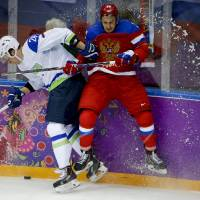 Photo - Russia defenseman Vyacheslav Voinov, right, collides with Slovenia forward Jan Urbas in the second period of a men's ice hockey game at the 2014 Winter Olympics, Thursday, Feb. 13, 2014, in Sochi, Russia. (AP Photo/Mark Humphrey)
