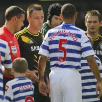 Photo -   Queens Park Rangers' Anton Ferdinand ignores the hand of Chelsea's John Terry, third left, during a pre-match handshakes before the start of their English Premier League soccer match at Loftus Road stadium, London, Saturday, Sept. 15, 2012. Chelsea's captain John Terry was acquitted in July of racially abusing Anton Ferdinand in last year's corresponding match. (AP Photo/Sang Tan)
