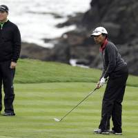 Photo - Former United States Secretary of State Condoleezza Rice, right, watches her ball roll up to the eighth green of the Pebble Beach Golf Links as playing partner D.A. Points, left, looks on during the second round of the AT&T Pebble Beach Pro-Am golf tournament on Friday, Feb. 7, 2014, in Pebble Beach, Calif. (AP Photo/Eric Risberg)