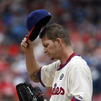 Photo - Philadelphia Phillies starting pitcher A.J. Burnett adjusts his hat after walking Los Angeles Angels' Hank Conger during the third inning of an interleague baseball game, Wednesday, May 14, 2014, in Philadelphia. (AP Photo)