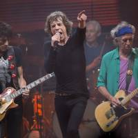 Photo - Mick Jagger, center, Ronnie Wood, left ,Charlie Watts, rear on drums and Keith Richards, right, of British band the Rolling Stones, perform on the Pyramid main stage at Glastonbury, England, Saturday, June 29, 2013. Thousands of music fans have arrived for the festival to see headliners, Arctic Monkeys, Mumford and Sons and the Rolling Stones.(Photo by Joel Ryan/Invision/AP)