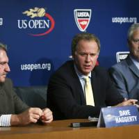 Photo - Patrick McEnroe, center, takes questions from reporters after he announced his resignation as the U.S. Tennis Association's general manager of player development at a news conference alongside David Haggerty, left, chairman, CEO and president of the USTA, and Gordon Smith, executive director and COO of the USTA, at the US Open, Wednesday, Sept. 3, 2014, in New York. (AP Photo/John Minchillo)
