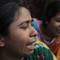 Photo - Relatives cry as rescuers look for survivors and victims at the site of a building that collapsed Wednesday in Savar, near Dhaka, Bangladesh,Thursday, April 25, 2013. By Thursday, the death toll reached at least 194 people as rescuers continued to search for injured and missing, after a huge section of an eight-story building that housed several garment factories splintered into a pile of concrete on Wednesday. (AP Photo/A.M.Ahad)