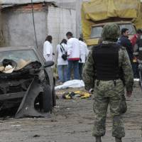 Photo - Soldiers guard the area as forensic workers gather evidence after a truck loaded with fireworks exploded during a religious procession in the town of Nativitas, Mexico, Friday March 15, 2013. A truck loaded with fireworks exploded during a religious procession in a rural village in central Mexico on Friday, killing at least nine people and injuring dozens more, authorities said. (AP Photo/J. Guadalupe Perez)