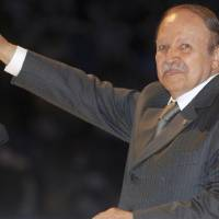 Photo -   FILE - In this Monday, April 6, 2009 file photo, Algerian President Abdelaziz Bouteflika, gestures, during his last campaign rally in Algiers. The 72-year-old president Bouteflika is running against five other candidates, all low-profile figures. Algerians riveted are a new string of corruption allegations against top officials that show all the signs of being a behind-the-scenes struggle ahead of key presidential elections in 2014.(AP Photo, File)