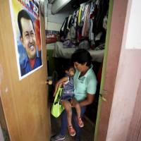 Photo -   In this Sept. 27, 2012 photo, a poster of Venezuela's President Hugo Chavez hangs on the door where Maria Perez carries her granddaughter out of the room where they live that was once a school room and is now part of a government provided shelter for families who lost their homes due to flooding, in Caracas, Venezuela. Fear of every stripe, like the loss of government housing like this one, permeates the intensely polarized election campaign, with many votes to be decided based not on the candidates' promises but rather on what worries people most. Chavez has continuously warning of chaos and the dismantling of the generous welfare state he built if he is voted out of office in the Oct. 7 vote. (AP Photo/Fernando Llano)
