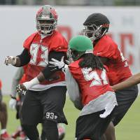 Photo -  Tampa Bay Buccaneers defensive tackle Gerald McCou (93) works against linebacker Damaso Munoz (57) and defensive tackle Euclid Cummings (95) during an NFL football minicamp Wednesday, June 11, 2014, in Tampa, Fla. (AP Photo/Chris O'Meara)   Chris O'Meara