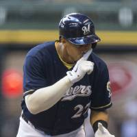 Photo - Milwaukee Brewers' Carlos Gomez looks back to the dugout after getting a lead off single against St. Louis Cardinals' Carlos Martinez during the first  inning of a baseball game Sunday, July 13, 2014, in Milwaukee. (AP Photo/Tom Lynn)