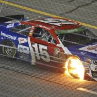 Photo - Clint Bowyer (15) heads to the pits with flames coming out of the wheel well during the NASCAR Sprint Cup auto race at Richmond International Raceway in Richmond, Va., Saturday, April 26, 2014. (AP Photo/Jason Hirschfeld)