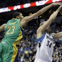 Photo - New Orleans Hornets' Anthony Davis, left, tries to block a shot by Minnesota Timberwolves' Greg Stiemsma in the second half of an NBA basketball game Saturday, Feb. 2, 2013 in Minneapolis. The Timberwolves won 115-86. Davis was called for a foul on the play. (AP Photo/Jim Mone)