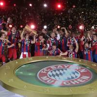 Photo - The team of German soccer club Bayern Munich celebrates with the trophy after winning the German Soccer Cup Final between FC Bayern Munich and Borussia Dortmund at the Olympic Stadium Berlin, Germany, Saturday, May 17, 2014. (AP Photo/Markus Schreiber)