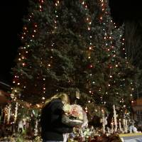 Photo - FILE - In this Thursday, Dec. 20, 2012 file photo, a woman with flowers walks past a Christmas tree which has become a memorial to the Newtown shooting victims in Newtown, Conn. In the wake of the shooting, the grieving town is trying to find meaning in Christmas. (AP Photo/Seth Wenig, File)