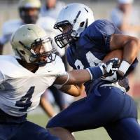 Photo - Edmond North's Ezel McIntee (24) avoids Southmoore's Johnathan Martin (4) during a high school football scrimmage at Moore Stadium in Moore, Okla., Friday, Aug. 17, 2012. Photo by Nate Billings, The Oklahoman