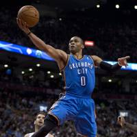 Photo - Toronto Raptors guard Jose Calderon (8) watches as Oklahoma City Thunder guard Russell Westbrook jumps to the hoop during first-half NBA basketball game action in Toronto, Sunday, Jan.6, 2013. (AP Photo/The Canadian Press, Frank Gunn) ORG XMIT: FNG106