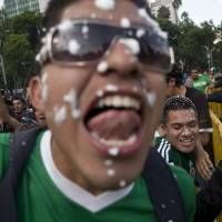 Photo - Mexico soccer fans celebrate at the Independence Monument after their team tied with Brazil in their 2014 World Cup soccer match, in Mexico City, Tuesday, June 17, 2014. Mexico claimed a deserved point against Brazil in a largely frustrating Group A game which finished 0-0 at Estadio Castelao in Fortaleza. (AP Photo/Rebecca Blackwell)