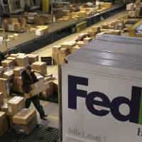 Photo - FILE - In this  Monday, Dec. 10, 2012, file photo, workers sort packages at a FedEx sorting facility in Kansas City, Mo. FedEx is more pessimistic about the U.S. economy than it was three months ago, but more assured of its own ability to grow earnings. The world's second-largest package delivery company lowered its economic forecast for the U.S., saying that there remains a lot of uncertainty for the company and the country. Its forecast for the current quarter, which incorporates the critical holiday season, falls short of Wall Street expectations. (AP Photo/Charlie Riedel, File)
