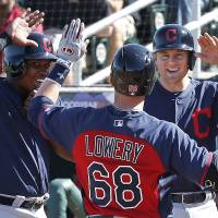 Photo - Cleveland Indians' Jake Lowery (68) is congratulated by Carlos Moncrief, left, and David Adams after hitting a grand slam against the Cincinnati Reds in the fifth inning of an exhibition baseball game in Goodyear, Ariz., Thursday, Feb. 27, 2014. (AP Photo/Paul Sancya)